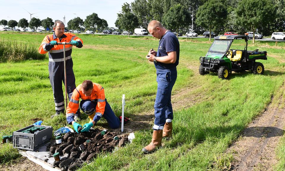 Medewerkers van een milieukundig onderzoeksbureau nemen grondmonsters