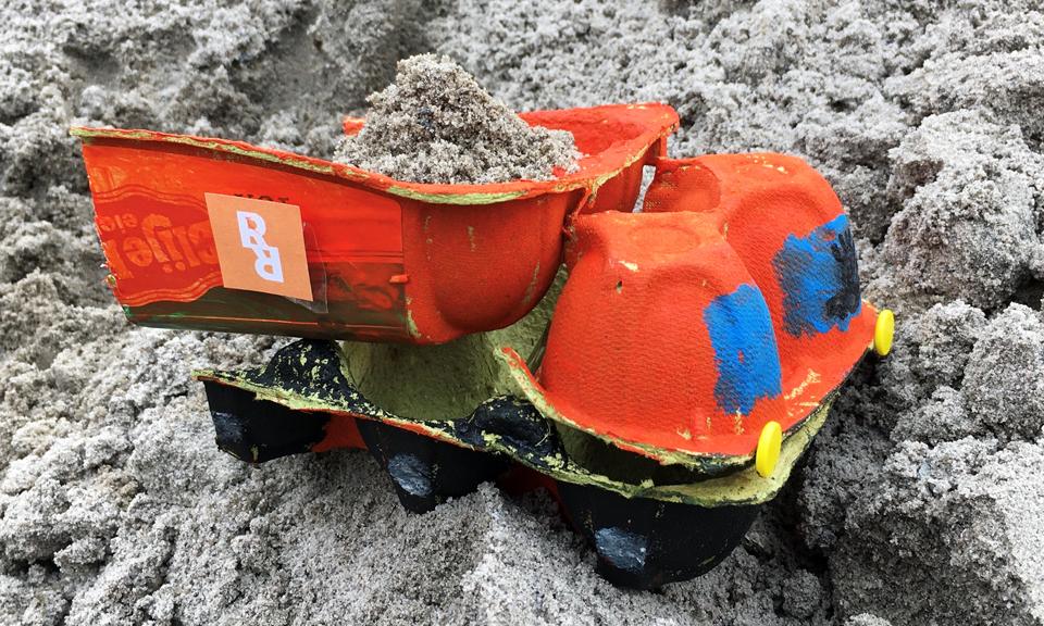Geknutselde kiepwagen in het zand