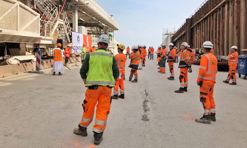 Genodigden staan op de bouwplaats voor de tunnelboormachine